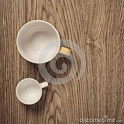 Two empty cups on wooden floor