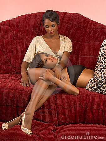 Two ethnic sexy women on sofa in retro clothes