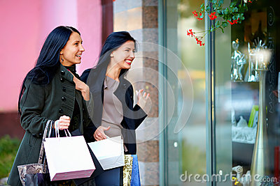 Two excited happy women looking in shop window