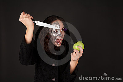 Two-faced witch with green apple and knife
