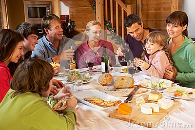 Two Familes Enjoying Meal In Alpine Chalet