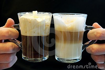Two fancy coffees in glass cups, held by two hands
