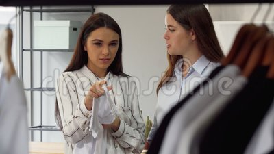 Two fashion store female workers discussing clothing on the display. Shot of two young cheerful female fashion store workers discussing displayed clothing for stock footage