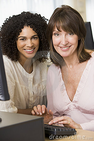 Two female adult students working on a computer