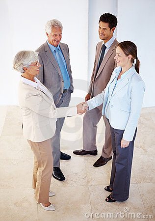 Two female executives shaking hands on deal