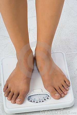 Two female feet on a bathroom scale