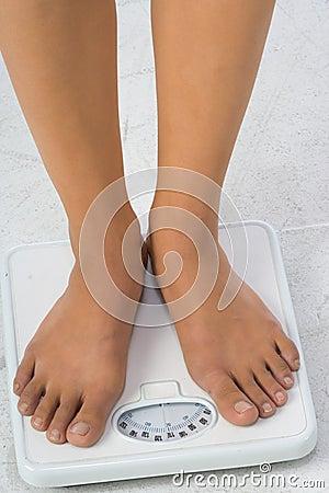 Two female feet on a bathroom scale