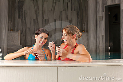Two female friends drinking tea in swimming pool