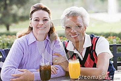 Two Female Friends Enjoying A Beverage By A Golf C