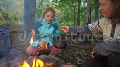 Two female friends make coffee in a kettle on an open fire in the forest during a hike. Two female friends make coffee in a kettle on an open fire in the forest stock footage