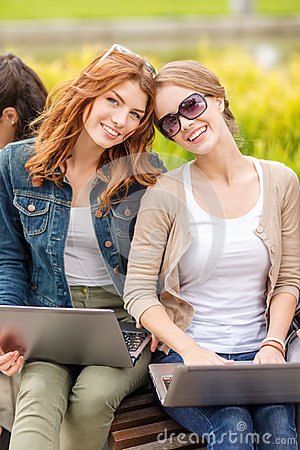 Two female students with laptop computers