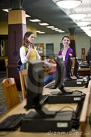 Two female students standing by library computers