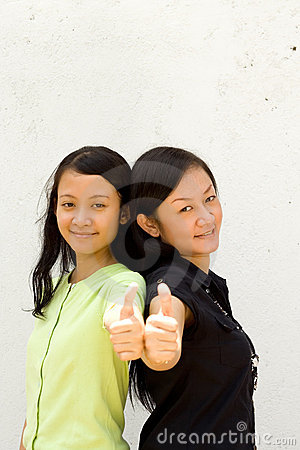 Two female teens giving thumbs up