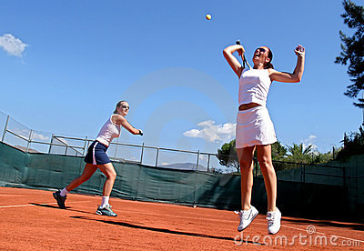 Two female tennis players playing doubles in the sun. One is leaping and stretching for the ball.