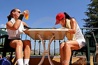 Two female tennis players sharing a joke after a game. Enjoying a glass of orange juice in the sun.