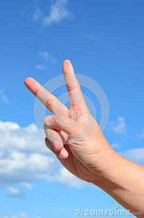 Two finger of human hand on blue sky