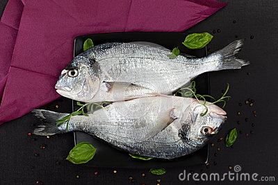 Two fish with fresh herbs on black plate.