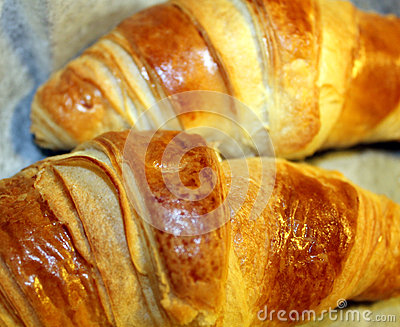 Two flaky baked croissants