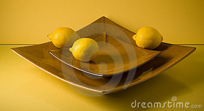 Two flat ceramic plates and three lemons on yellow