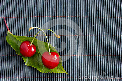 Two fresh cherries and a leaf on bamboo tablecloth