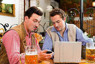 Two friends in Bavarian pub with laptop