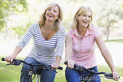 Two friends on bikes outdoors smiling