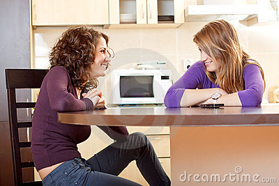 Two friends chatting sitting on a kitchen table