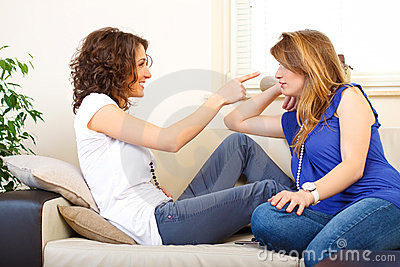 Two friends on a couch laughing and having fun