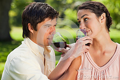 Two friends drinking wine while linking arms