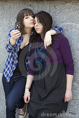 Two friends having a blast with a phone.