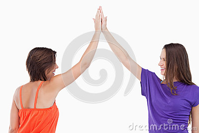 Two friends joining their hands in the air