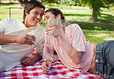 Two friends laughing as they raise their glasses during a picnic