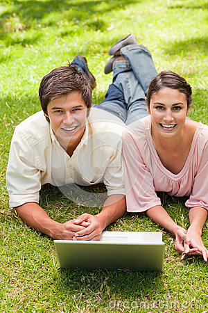 Two friends laughing while looking ahead as they use a laptop