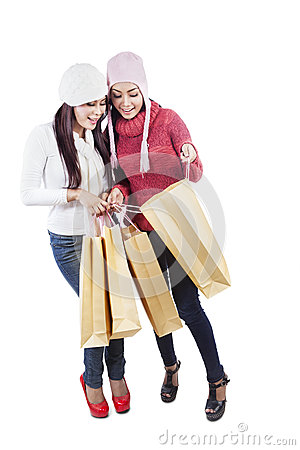 Two friends look shopping bags isolated in white