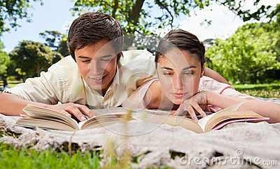 Two friends looking down at books while lying on a blanket