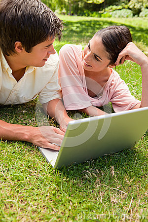 Two friends looking at each other as they use a laptop together