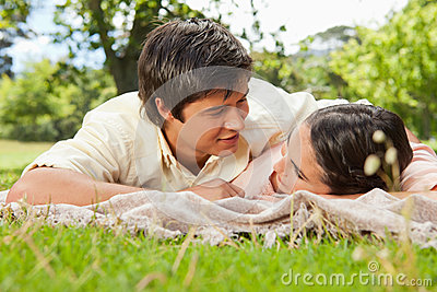 Two friends looking into each others eyes while lying on a blank