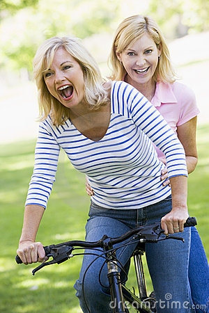 Two friends on one bike outdoors smiling