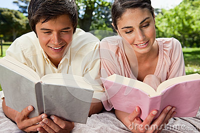 Two friends smiling as they read while lying on a blanket