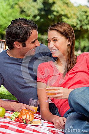 Two friends smiling each other while they hold glasses