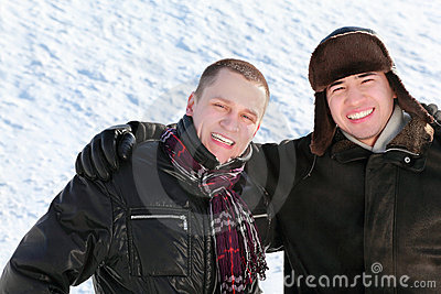 Two friends stand on snow in embrace and smile
