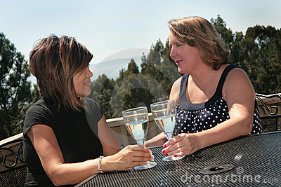Two Friends Talking While Drinking White Wine