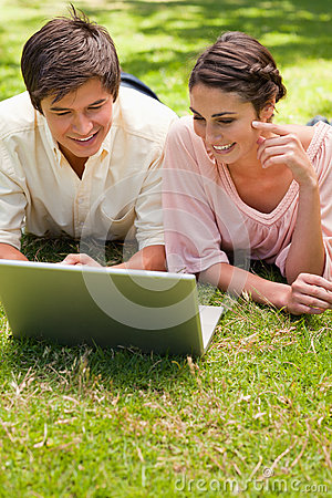 Two friends using a laptop together