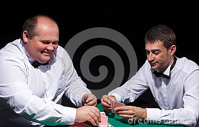 Two gentlemen in white shirts, playing cards