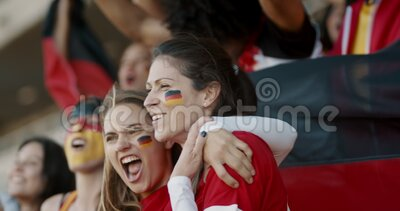 Enthusiastic German fans cheering in game. Two german female friends enjoying watching a game. German soccer fans cheering for their national team stock video