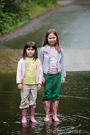 Two gilrs standing in a stream