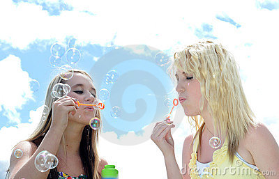 Two girl friends blowing bubbles