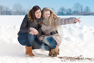 Two girl friends pointing in winter snow