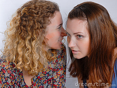 Two girl friends sharing a secret
