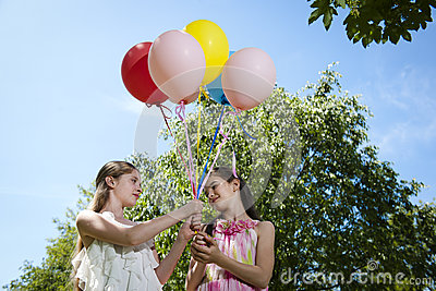 Two girlfriends with balloons
